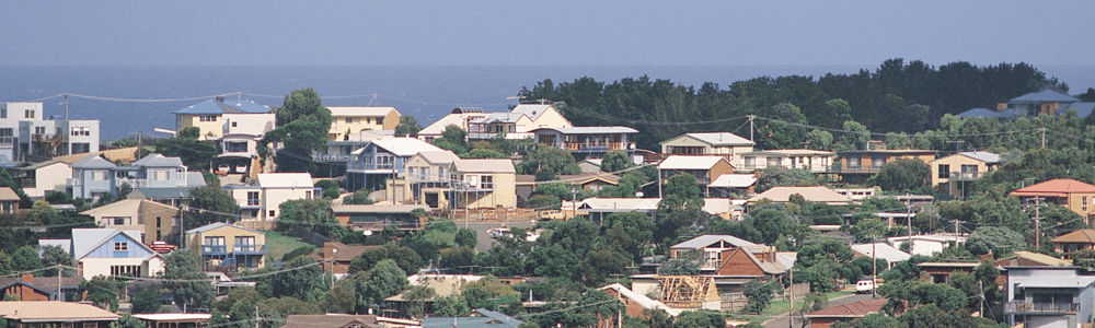 Image shows houses situated in a beachside town, the ocean can be seen in the background.